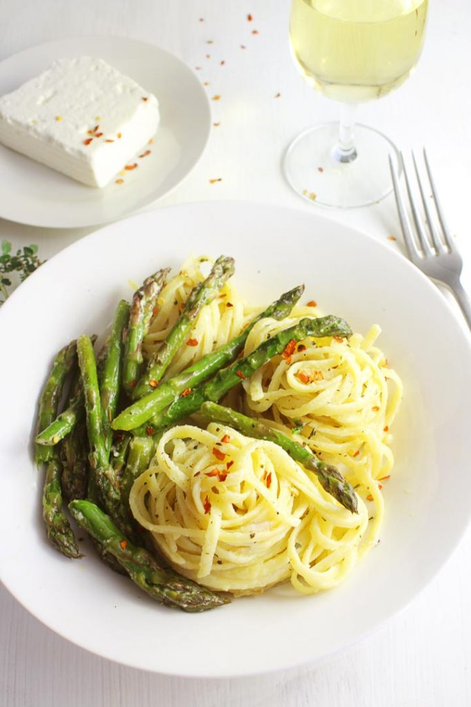 Asparagus pasta with feta cheese on a plate with feta piece and a glass of white wine