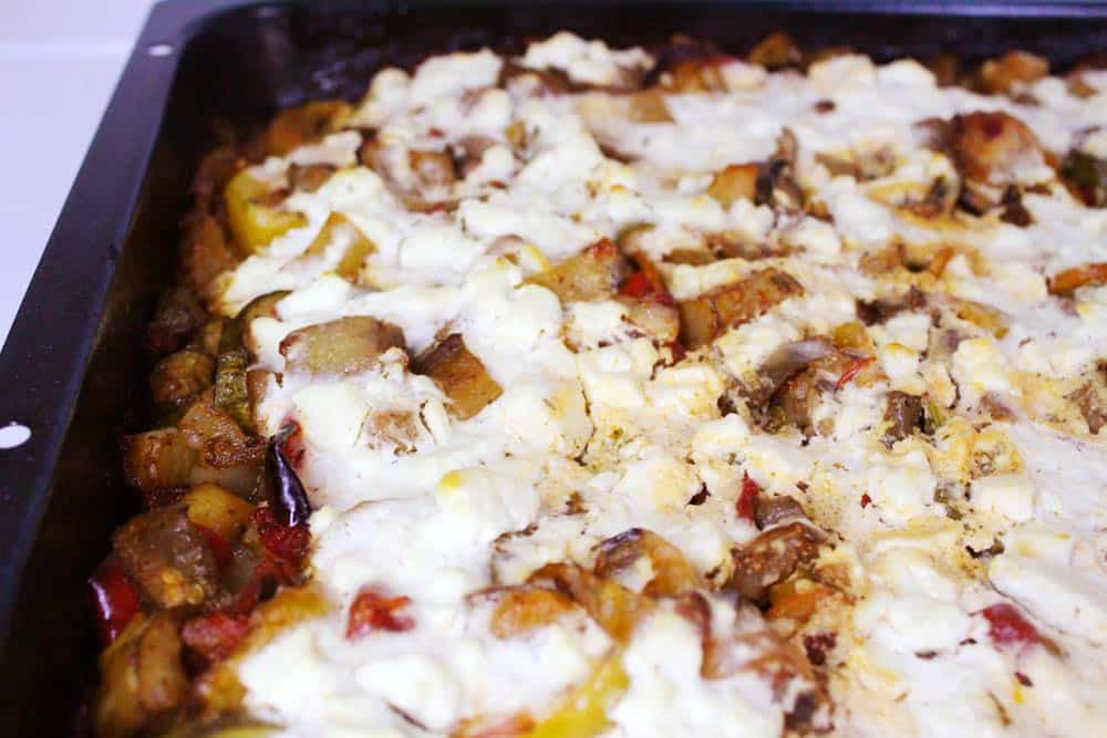 Baking pan with a layer of vegetables and yogurt-feta dressing