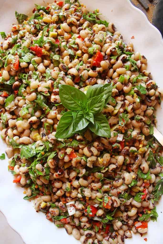 Black eyed peas salad in a big white platter with basil for decoration