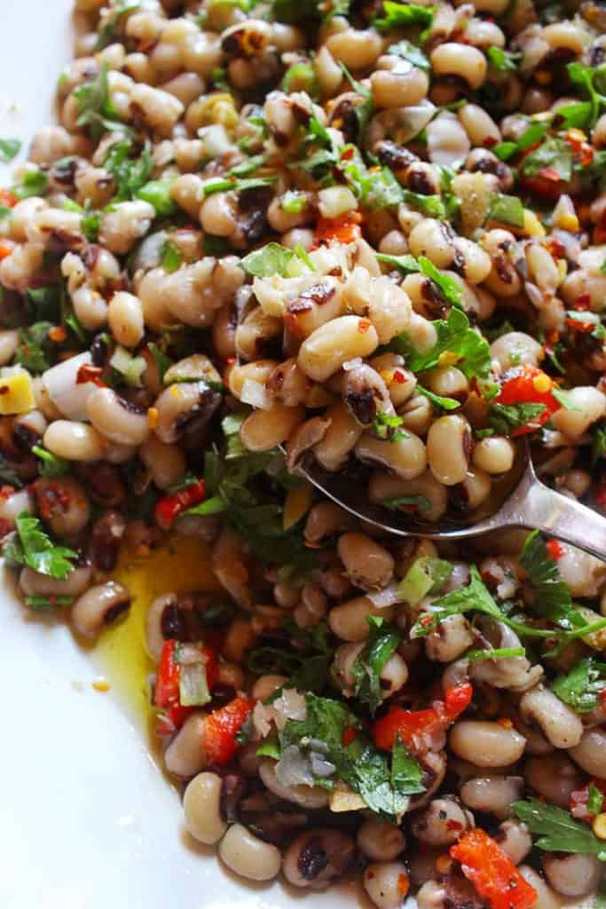 Black-eyed peas in platter with a tablespoon full with black-eyed peassalads